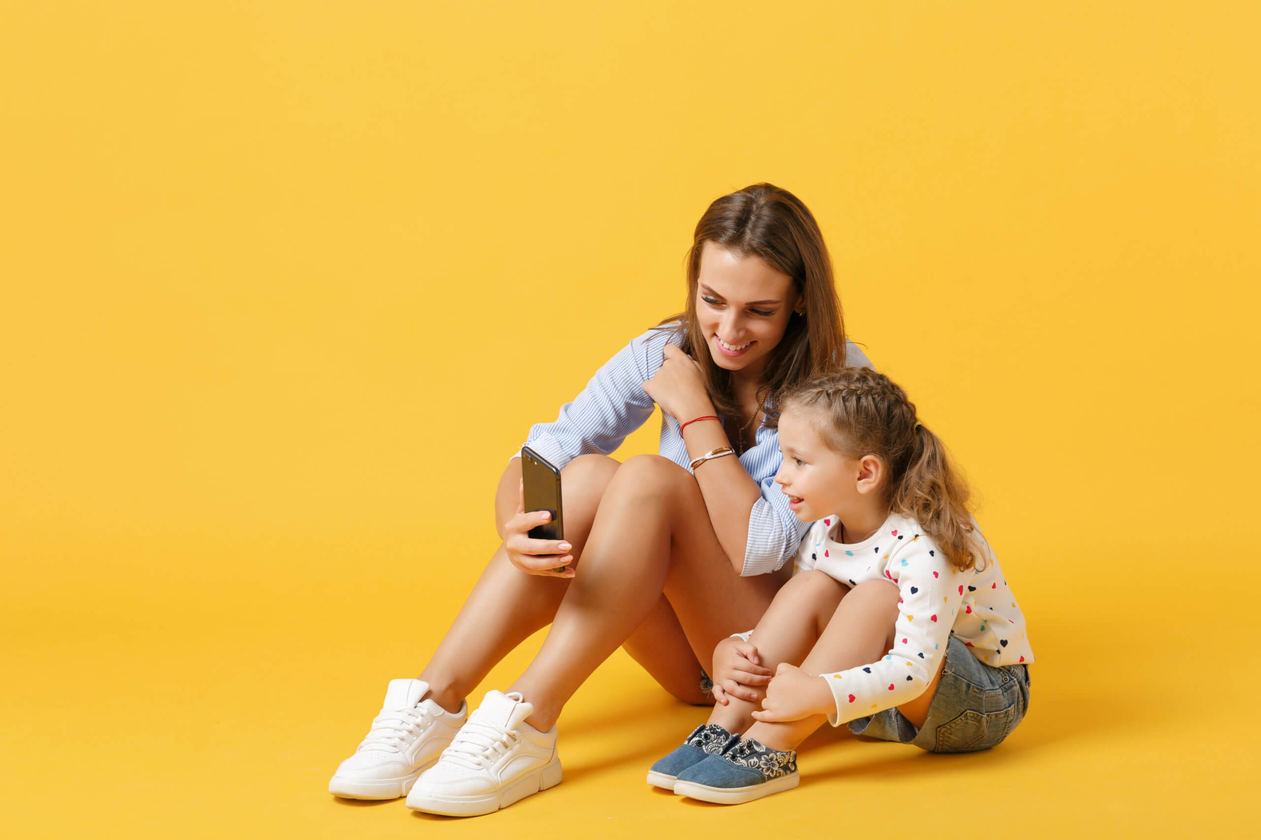 Woman using mobile phone have fun with cute child baby girl 4-5 years old. Mommy little kid daughter