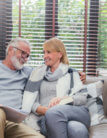 elderly couple happily sitting together on a couch